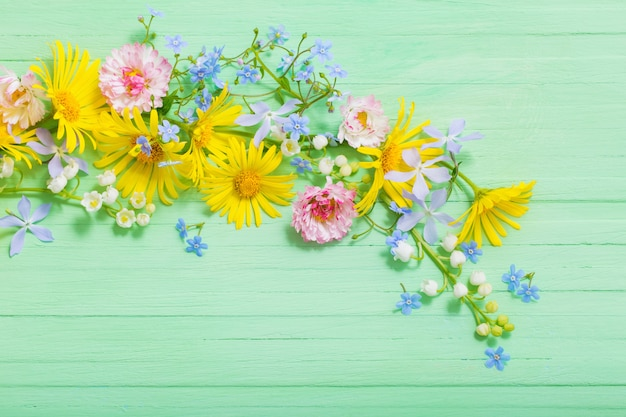 Рамка из красивых цветов на зеленом деревянном