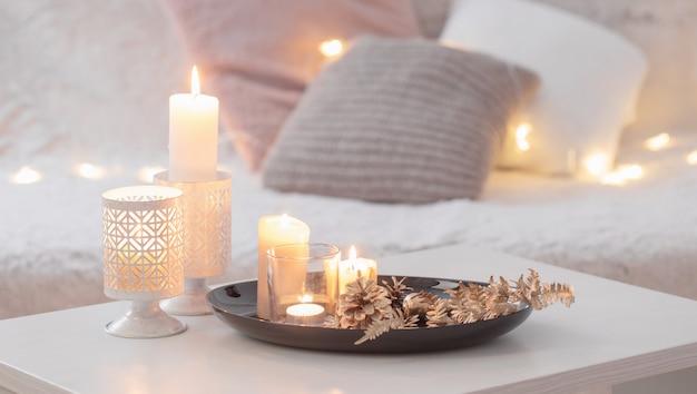 Новогоднее украшение с зажженными свечами на белом столе на фоне дивана с пледами и подушками.
