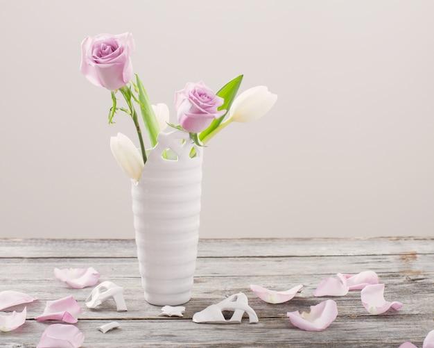 古い木製のテーブルの上に壊れた花瓶にピンクのバラ
