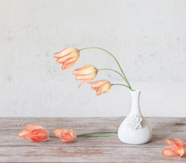 木製のテーブルの上に白い花瓶のチューリップ