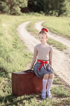 Красивая девушка на чемодане на открытом воздухе