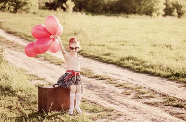 Красивая девушка на чемодане с красными воздушными шарами на открытом воздухе