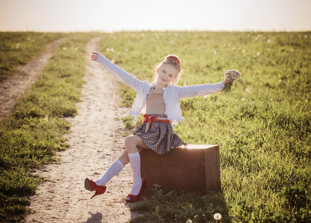 Красивая девушка на чемодане с цветами на открытом воздухе