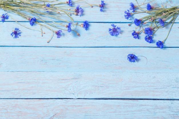 青い木製の背景上のヤグルマギク
