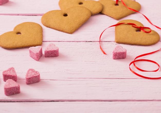Печенье сердце на розовом деревянном пространстве