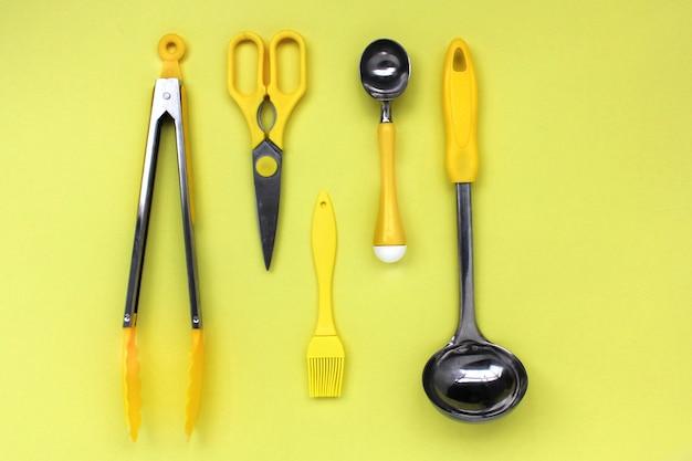 Кухонные принадлежности ковша, ножницы, щипцы, кисточка, ложка желтого мороженого на желтом фоне
