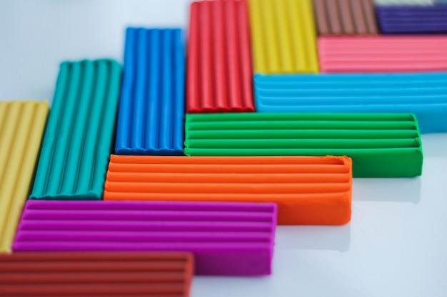 Разноцветный пластилин - это материал для творчества с детьми. моделирование и развитие мелкой моторики. школьные принадлежности на голубом