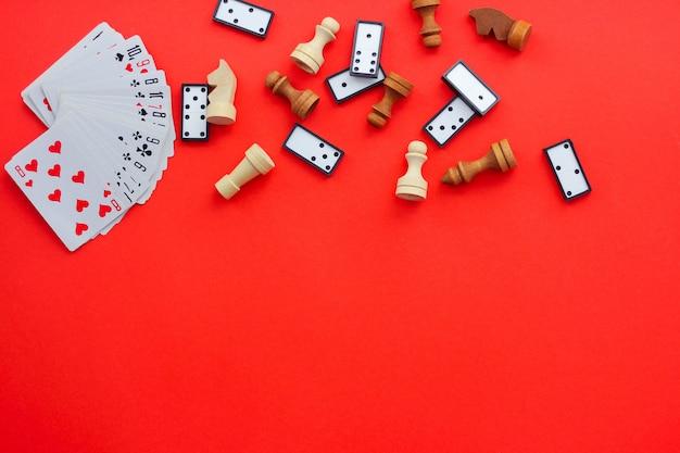 Настольные игры на красном фоне: игральные карты, шашки и шахматы. вид сверху, место под текстом