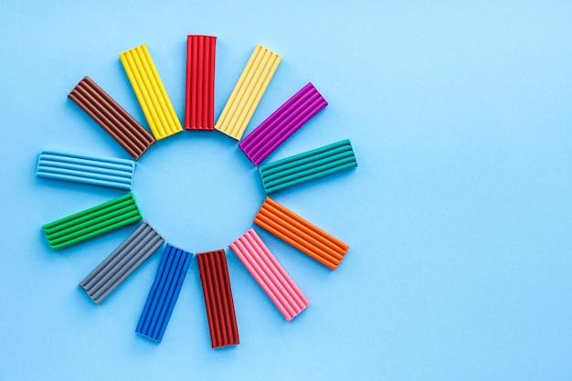Разноцветный пластилин - это материал для творчества с детьми. моделирование - развитие мелкой моторики. на синем фоне, вид сверху.