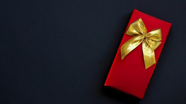 黒地に金の弓と赤いボックス。贈り物のコンセプト