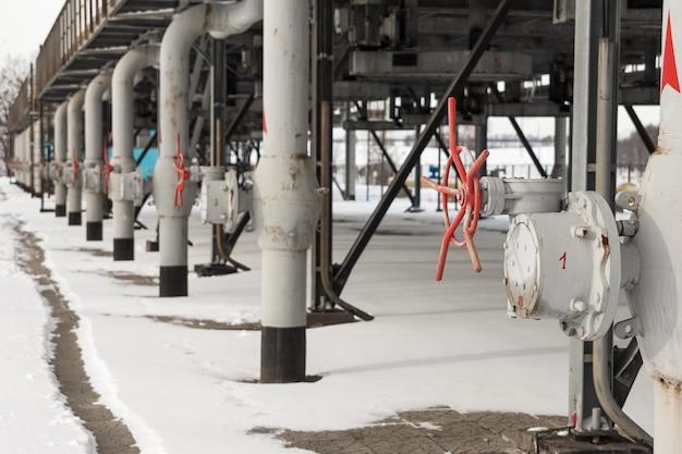 冬に撮影されたガス圧縮ステーションの赤いバルブでガスを供給する灰色の金属管。ガス圧縮機ステーションでのガス輸送のためのチューブ構造の眺め