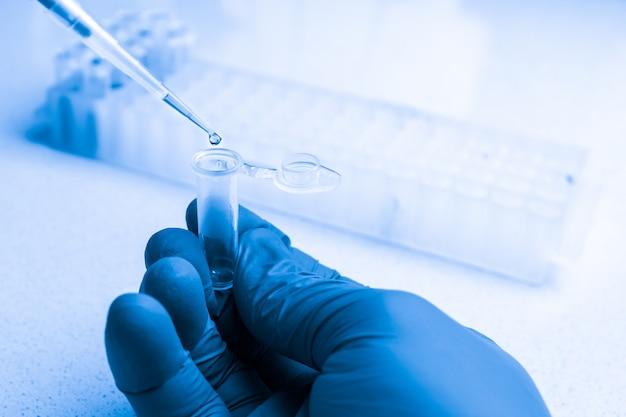 コロナウイルスに対する新しいワクチンまたは医薬品の合成。化学分析の進行中の臨床検査室。自動ピペットを使用したプローブの収集。
