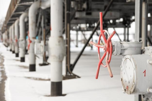 冬に撮影されたガス圧縮ステーションの赤いバルブでガスを供給する灰色の金属管。冬のガス圧縮ステーションでのガス輸送のためのチューブ構造の眺め