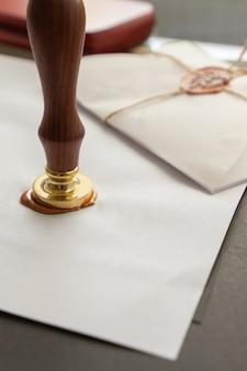 Государственный нотариус с восковой печатью. белый конверт с коричневой сургучной печатью, золотой штамп. адаптивный дизайн макета, плоская планировка. натюрморт с почтовыми принадлежностями.