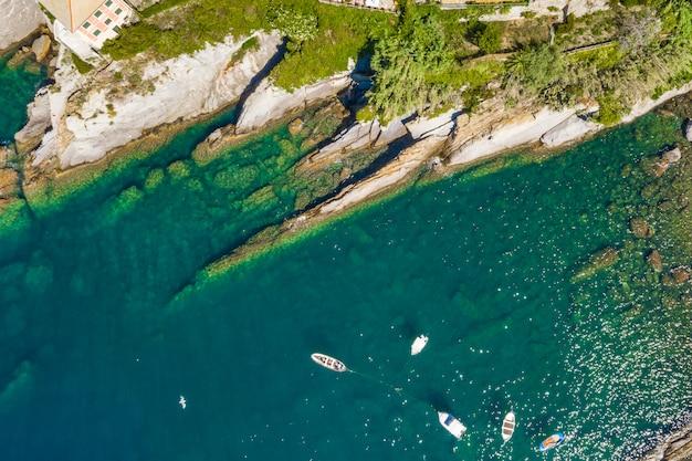 カモーリ岩が多い海岸の空撮。港の近くに緑の水が停泊するボートとヨット。