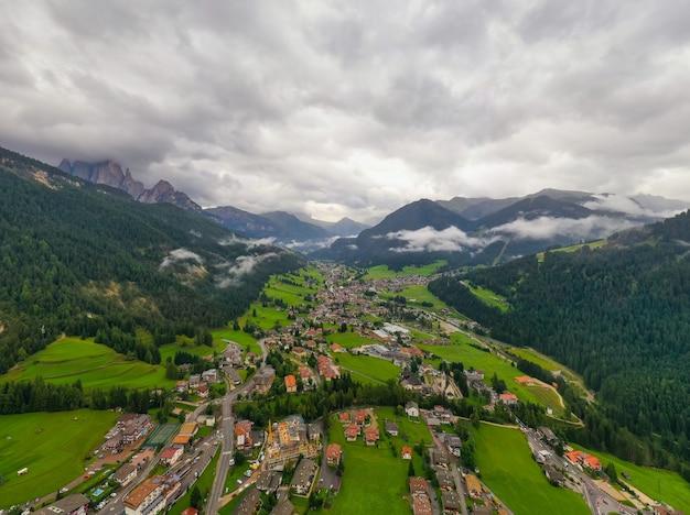 Красивый воздушный панорамный взгляд доломитов альпов, италии. горы покрыты облаками и туманом. катиначчо горные хребты. долина фасса