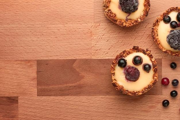 Здоровые хлопья кексы с ягодами и желтый крем на деревянный стол.