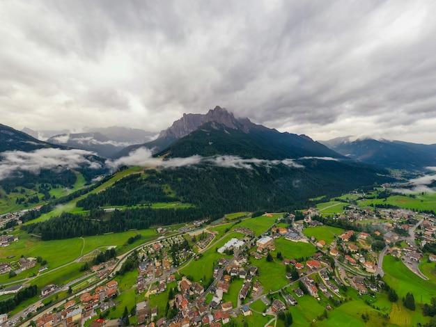 Красивый воздушный панорамный взгляд доломитов альпов, италии. горы покрыты облаками и туманом. катиначчо горные хребты. долина фасса, валь ди фасса