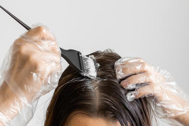 Руки женщины крупного плана крася волосы используя черную щетку. окрашивание седых волос в домашних условиях.