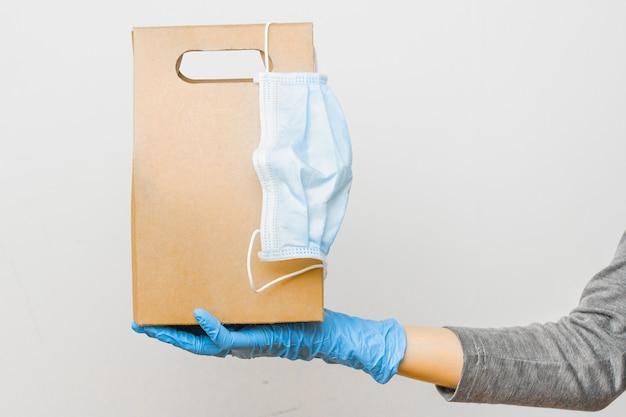 検疫中の配送サービスのコンセプト。それを防護マスクと段ボールの袋を持つ女性の手。オンラインショップからの安全な配達。