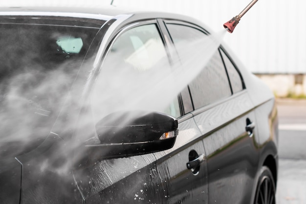 男はセルフサービスの洗車で車を洗っています。水できれいな高圧車両洗浄機。洗車設備、ムラダボレスラフ、