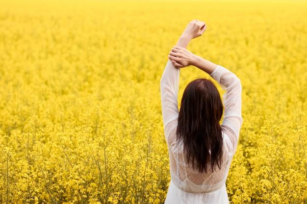 白いドレスを着た若い女性は、菜の花が咲く黄色のフィールドで頭の上に手を挙げた。コピースペースと春の結婚式の写真の概念。