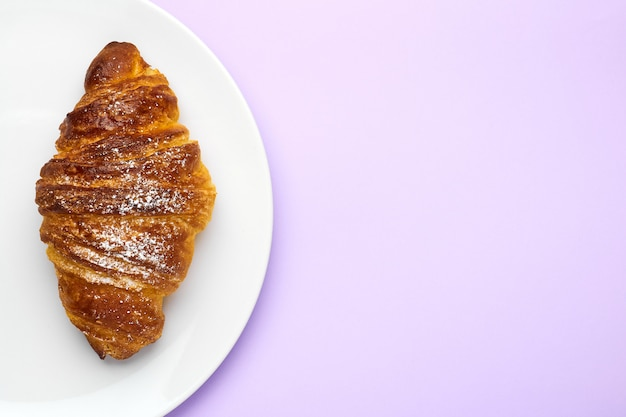 Свежеиспеченные французские круассаны на белом фоне на фиолетовом фоне с копией пространства. концепция рекламы традиционной выпечки.