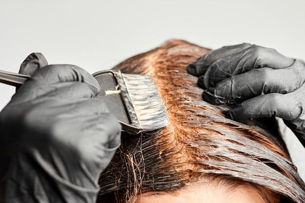 Руки женщины крупного плана крася волосы используя черную щетку.