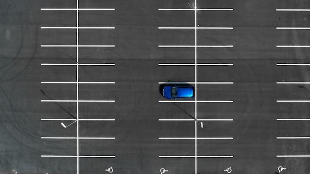 Вид сверху на пустые парковки с одной синей машиной