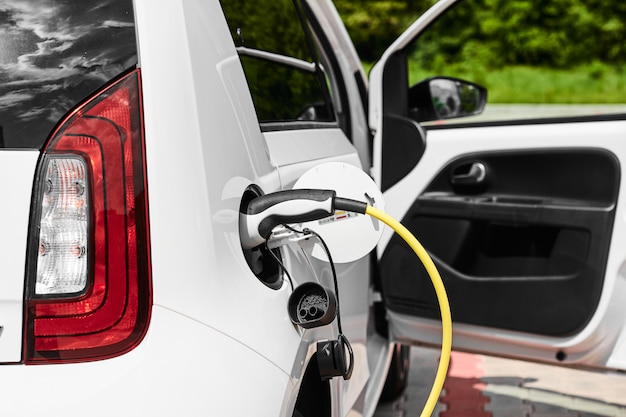 Желтая электрическая розетка зарядки электромобиля на улице. блок питания подключен к электромобилю