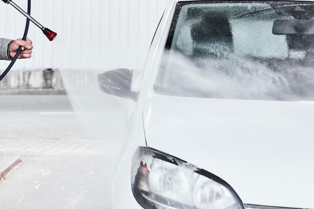 高圧水を使用して白い車を洗うマンの手を閉じる。車の自己洗浄サービス