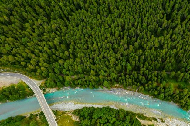 スイスの森を流れるイン川。山の青い川のドローンから空撮
