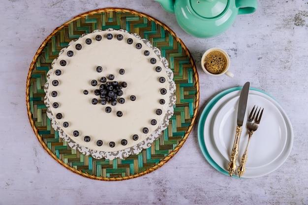 Белый торт со свежей черникой на вершине, кофе и тарелки.