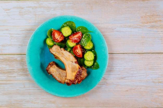 Свиные ребрышки с соусом барбекю и свежим салатом на синей тарелке.