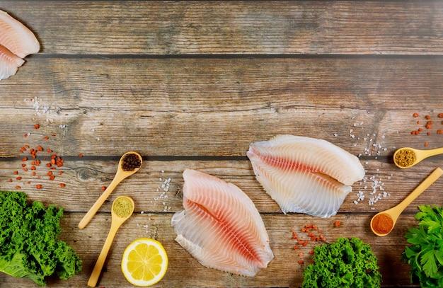 レモンとスパイスのテーブルのティラピアの未調理の魚の切り身。
