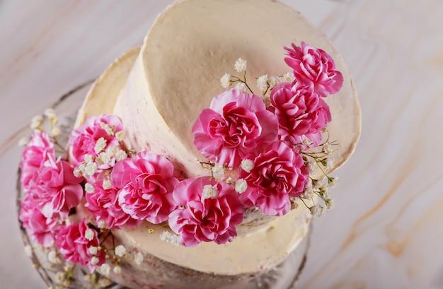 花で飾られた自家製の結婚式裸層ケーキ