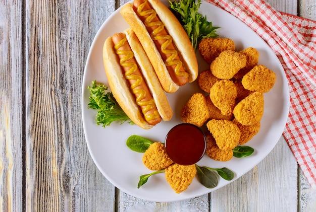 パン粉チキンナゲットと白い皿にマスタードのホットドッグ。