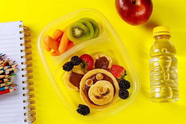果物とニンジンの変な顔のパンケーキを持つ子供のための学校のランチボックス。