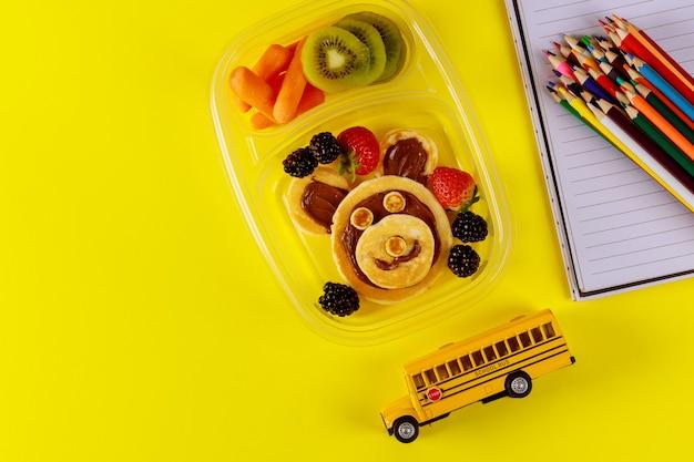 Школьная коробка с блинами, свежими фруктами и игрушкой школьного автобуса.
