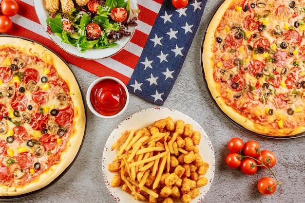 Партия пиццы на американский праздник на деревянном столе.