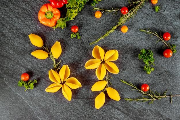 Сухая скорлупа макаронных изделий напоминает цветок с томатами черри и сладким перцем.