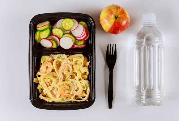 水とリンゴと一緒に食品容器で食べる準備ができた食事。
