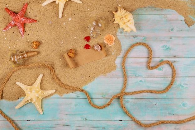 Сердце из веревки на дереве с песком, ракушками, песком и морской звездой