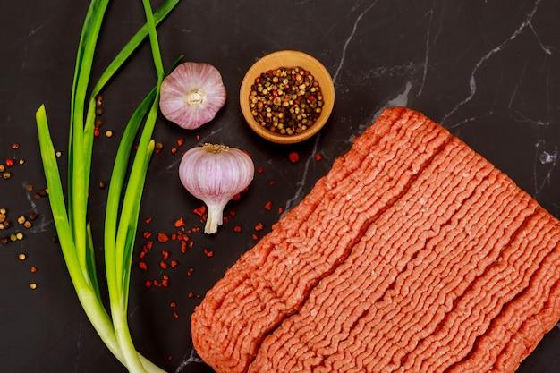Сырой говяжий фарш с чесноком и зеленым луком на черной поверхности