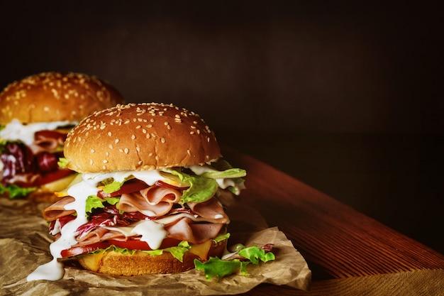 Вкусные бутерброды со свежими овощами и ветчиной на деревянной доске