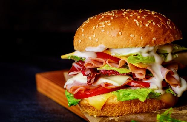 Бутерброд с ветчиной, листьями салата, сыром и помидорами