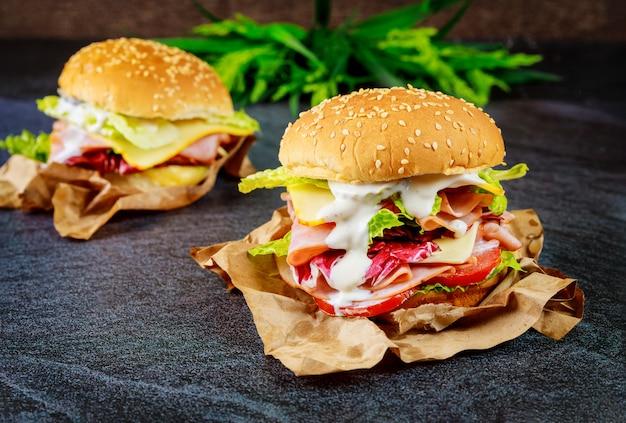 Два бутерброда с ветчиной, сыром, помидорами, листьями салата на темной поверхности