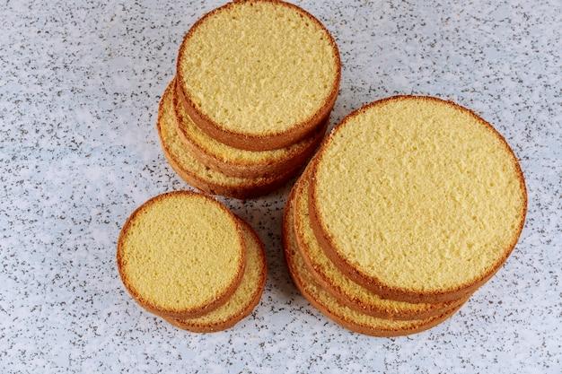 ウエディングケーキを作るためのテーブルの上の柔らかいケーキをスライス