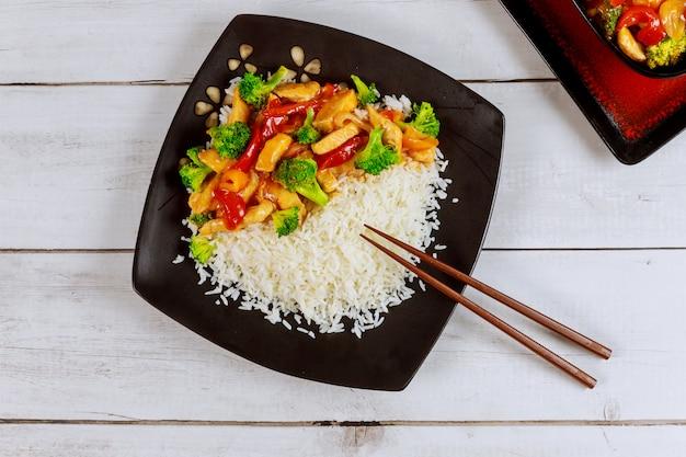 Жареная курица с рисом и овощами на квадратной тарелке с палочкой для еды