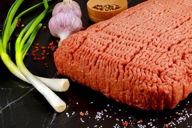 Сырой говяжий фарш с чесноком и луком на черной поверхности